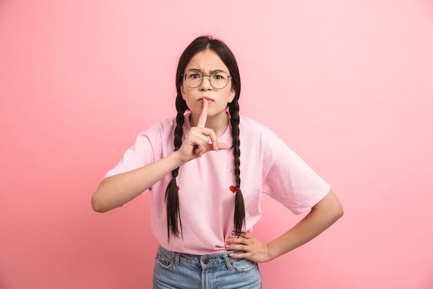 Młoda nastolatka z dwoma warkoczami w okularach, trzymająca palec wskazujący na ustach i prosząca o zachowanie ciszy na tle różowej ściany