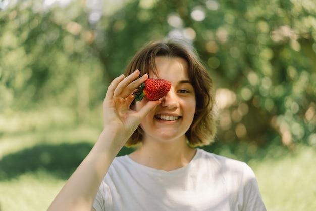 Młoda nastolatka z truskawką w koszulce w plenerze i patrząca na kamery ludzie i życie...