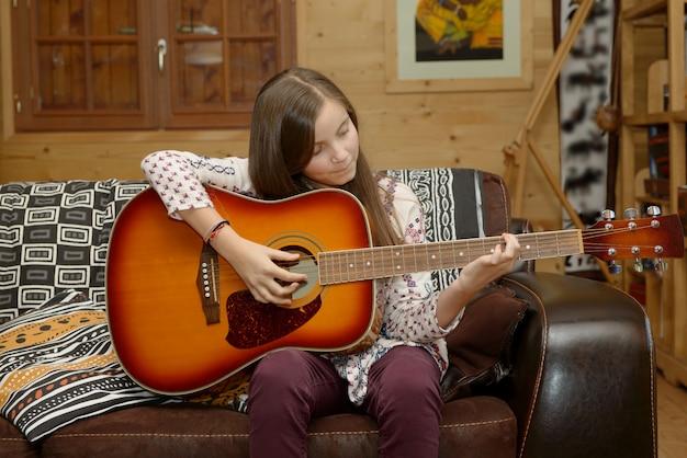Młoda nastoletnia dziewczyna bawić się gitarę akustyczną