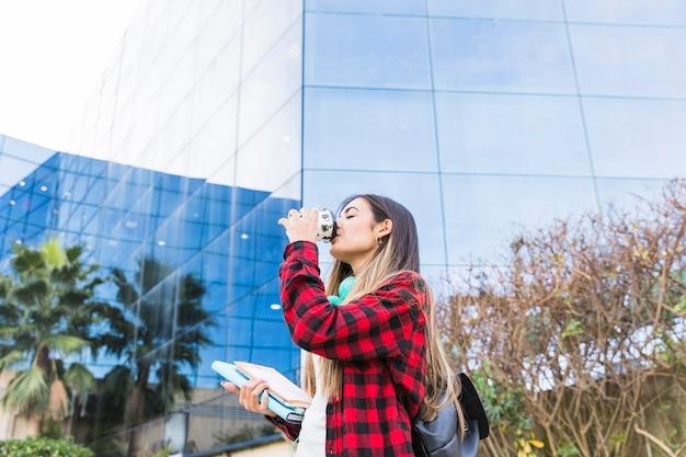 Młoda nastoletnia dziewczyna stoi przed uniwersyteckim budynkiem pije na wynos kawę