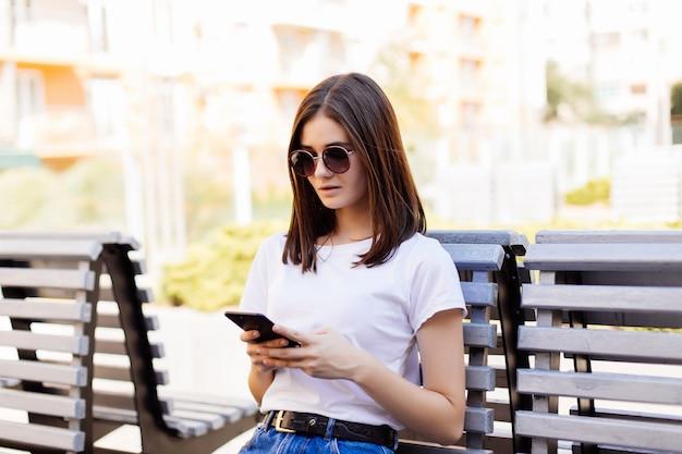 Młoda nastoletnia dziewczyna używa mądrze telefon i texting siedzieć w ławce miastowy park