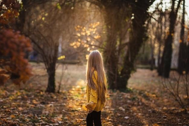 Młoda nastoletnia dziewczyna z długim blondynem w żółtym pulowerze pozuje w jesień parku. skopiuj miejsce