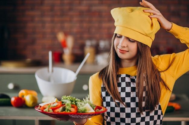 Młoda nastoletnia dziewczyny narządzania sałatka dla śniadania przy kuchnią