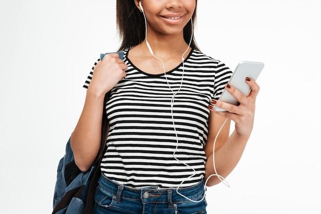 Młoda nastoletnia kobieta z plecakiem słucha muzyka przez słuchawek