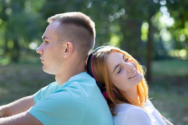 Młoda nastoletnia para wpólnie outdoors w lato parku. dziewczyna z rudymi włosami, słuchanie muzyki w słuchawkach i chłopiec jest znudzony.
