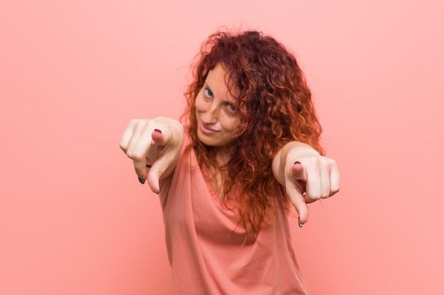 Młoda, naturalna i autentyczna ruda kobieta radośnie uśmiecha się do przodu.