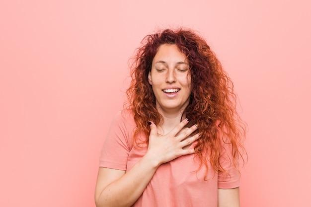 Młoda, naturalna i autentyczna ruda kobieta śmieje się głośno trzymając dłoń na piersi.