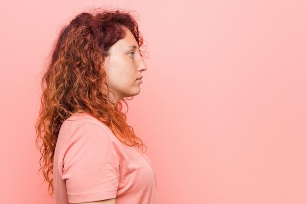 Młoda naturalna i autentyczna ruda kobieta spoglądająca w lewo, z boku.