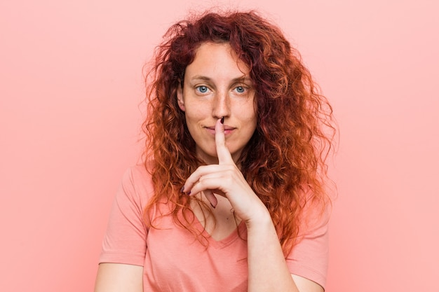Młoda naturalna i autentyczna rudowłosa kobieta trzymająca sekret lub prosząca o ciszę.