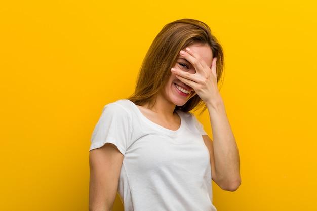 Młoda naturalna kaukaska kobieta mruga palcami do kamery, zakłopotana zakrywając twarz.