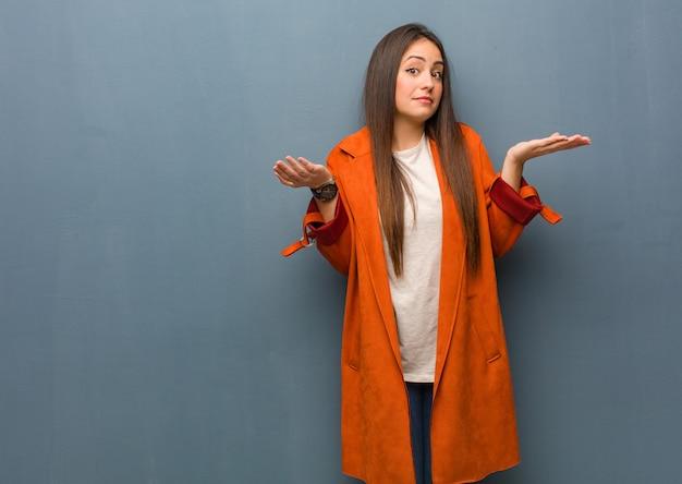 Młoda naturalna kobieta wątpi i wzrusza ramionami