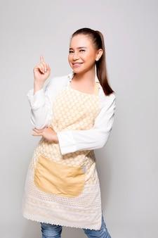 Młoda naturalna kobieta wskazuje up z palcem w fartuchu