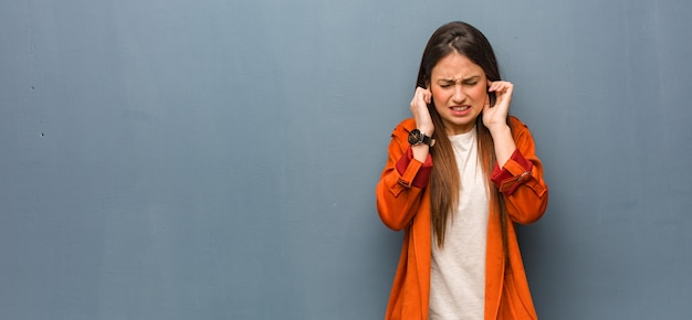 Młoda naturalna kobieta zakrywa ucho z rękami