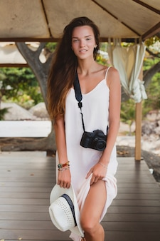 Młoda naturalna piękna kobieta w bladej sukni pozowanie w namiocie, tropikalne wakacje