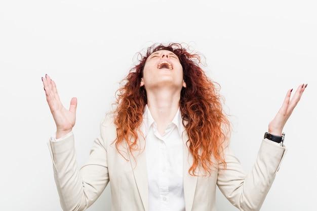 Młoda naturalna ruda kobieta biznesu krzyczy do nieba, patrząc w górę, sfrustrowana.