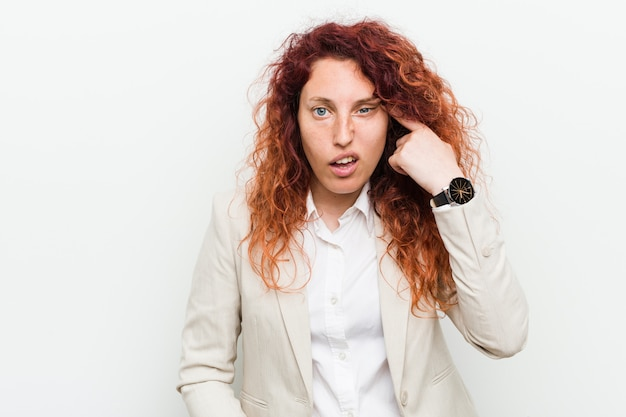 Młoda naturalna rudzielec biznesowa kobieta odizolowywająca przeciw białemu tłu pokazuje rozczarowanie gest z palcem wskazującym.