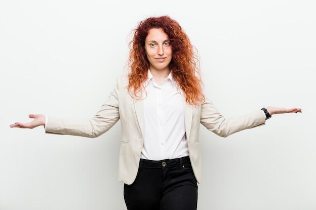 Młoda naturalna rudzielec biznesowa kobieta odizolowywająca przeciw bielowi pokazuje mile widziany wyrażenie.