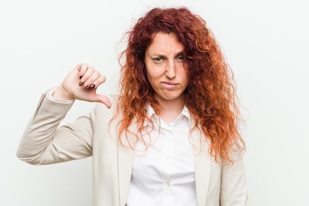 Młoda naturalna rudzielec biznesowa kobieta odizolowywająca przeciw bielowi pokazuje niechęć gest, kciuki zestrzela. nieporozumienie