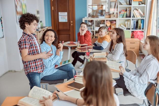 Młoda nauczycielka czytająca ze swoim uczniem przed całą klasą. dzieci ze szkoły podstawowej siedzą na biurkach i czytają książki w klasie.