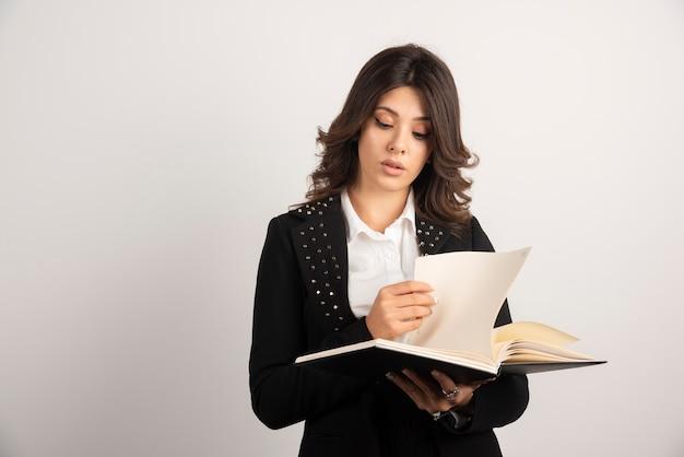 Młoda nauczycielka patrząc przez notatnik na białym tle.