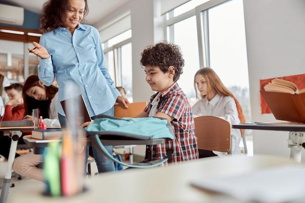 Młoda nauczycielka pomaga czytać swojemu uczniowi. dzieci ze szkoły podstawowej siedzą na biurkach i czytają książki w klasie.