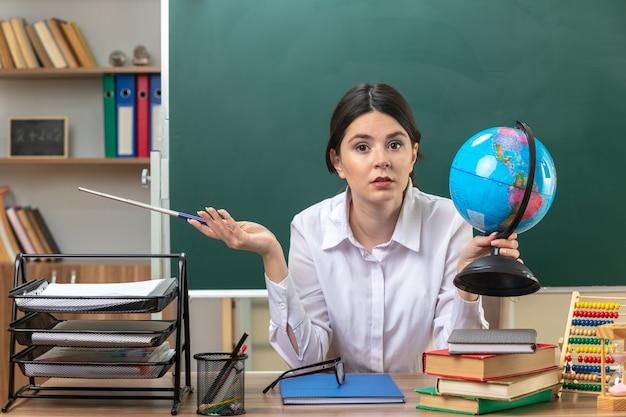 Młoda nauczycielka siedząca przy stole z narzędziami szkolnymi trzymająca kulę ziemską z kijem wskaźnikowym w klasie zadowolona rozkładająca rękę