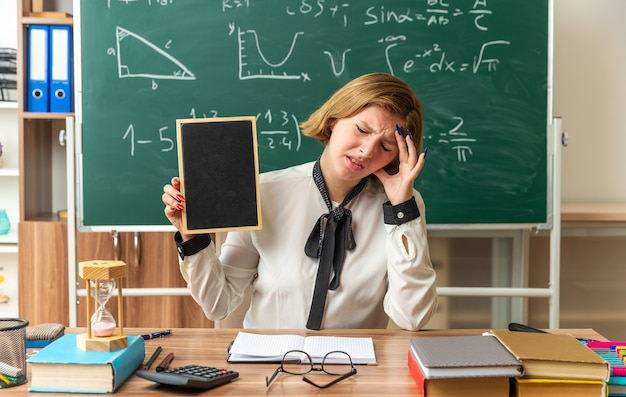 Młoda nauczycielka siedzi przy stole z przyborami szkolnymi i trzyma mini tablicę w klasie