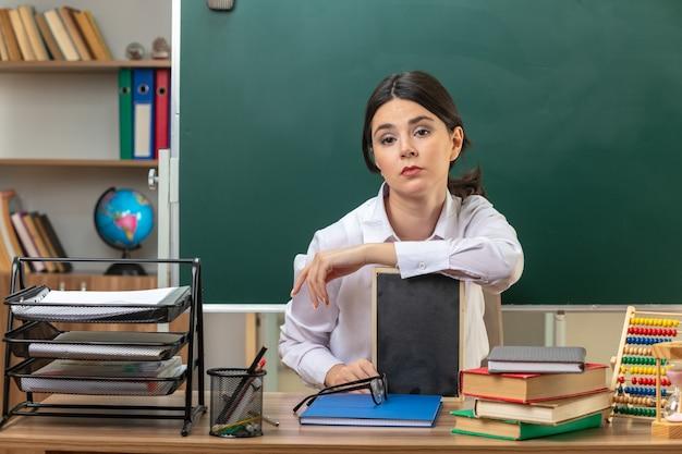 Młoda nauczycielka siedzi przy stole z szkolnymi narzędziami, trzymając mini tablicę w klasie