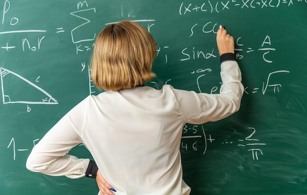 Młoda nauczycielka stojąca przed tablicą i pisząca coś na tablicy z linką do tablicy w klasie in