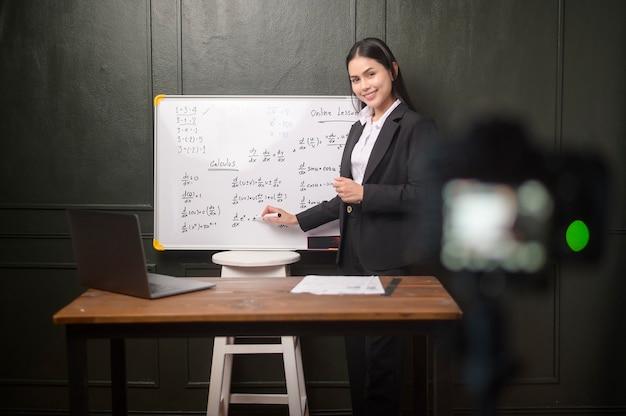 Młoda nauczycielka używa kamery do nagrywania lekcji online podczas kwarantanny, edukacji online, koncepcji nauczania na odległość