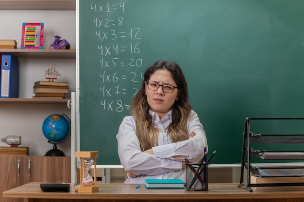 Młoda nauczycielka w okularach patrząc na przód zdezorientowana i niezadowolona z rękami skrzyżowanymi siedzi przy ławce szkolnej przed tablicą w klasie