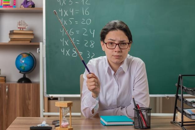 Młoda nauczycielka w okularach, patrząc z przodu z poważnym wyrazem pewności siebie, trzymając wskaźnik, wyjaśniając lekcję siedząc przy ławce szkolnej przed tablicą w klasie