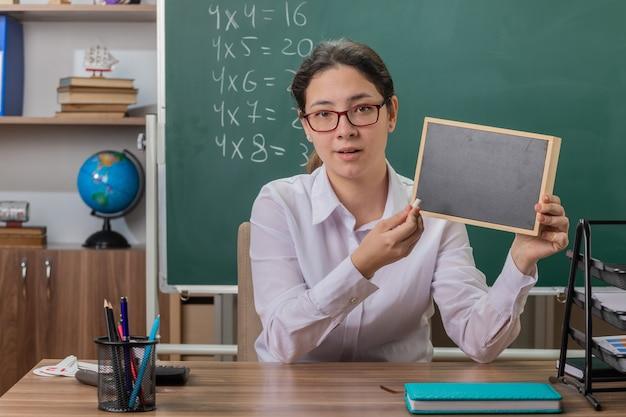 Młoda nauczycielka w okularach trzyma małą tablicę i kawałek kredy wyjaśniający lekcję patrząc na przód uśmiechnięty pewny siebie siedzi przy ławce szkolnej przed tablicą w klasie