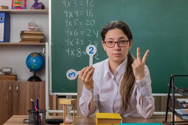 Młoda nauczycielka w okularach trzymająca tablice rejestracyjne wyjaśniająca lekcję pokazująca numer dwa z palcami wyglądająca pewnie siedzi przy ławce szkolnej przed tablicą w klasie