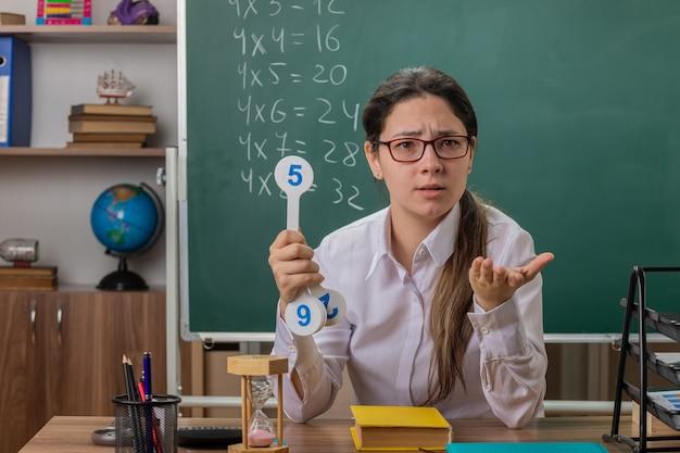 Młoda nauczycielka w okularach trzymająca tablice rejestracyjne, wyjaśniająca lekcję, zdezorientowana z wyciągniętą ręką, prosząca siedząc przy szkolnej ławce przed tablicą w klasie