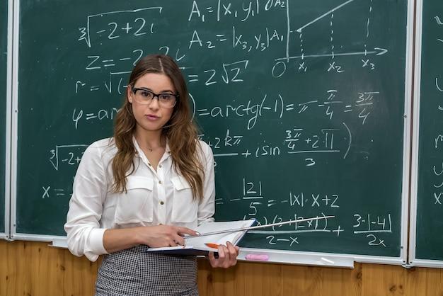 Młoda nauczycielka w sali szkolnej podczas zajęć, przy tablicy z zapisanymi wzorami matematycznymi. edukacja