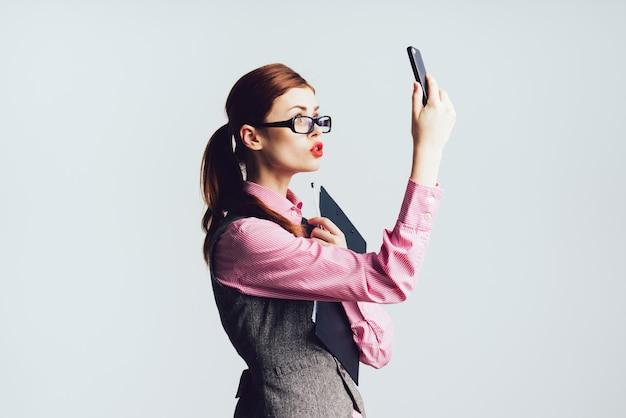 Młoda nauczycielka z rudymi włosami w okularach trzyma telefon w dłoni, podniosła telefon do góry