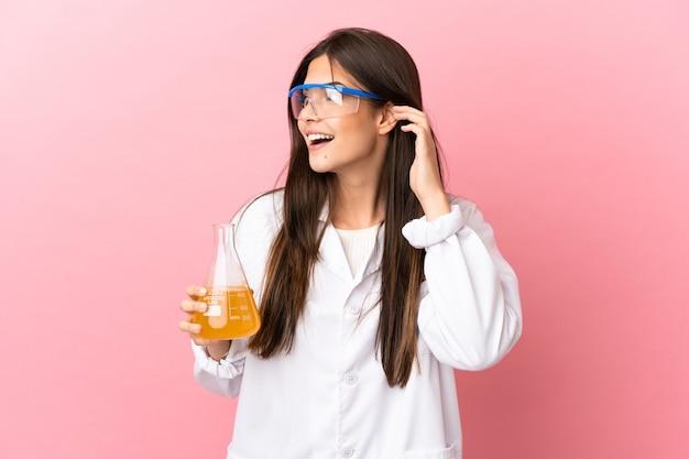 Młoda naukowa dziewczyna na na białym tle różowym tle, słuchając czegoś, kładąc rękę na uchu