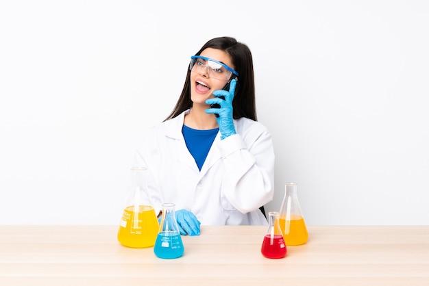 Młoda naukowa kobieta w tabeli, prowadząc rozmowę z telefonem komórkowym