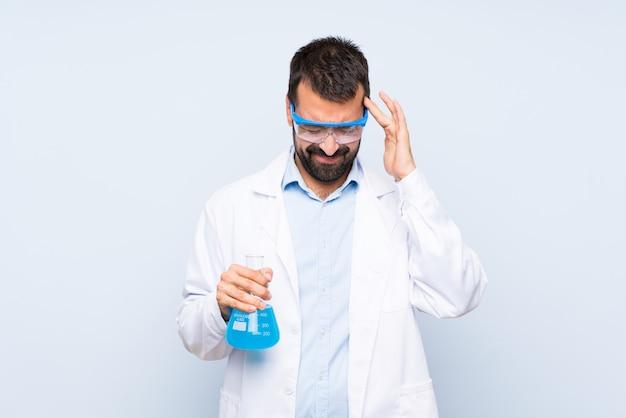 Młoda naukowa trzyma laborancka kolba nad odosobnioną ścianą z migreną