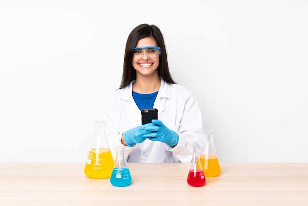 Młoda naukowiec kobieta w tabeli wysyłanie wiadomości z telefonu komórkowego