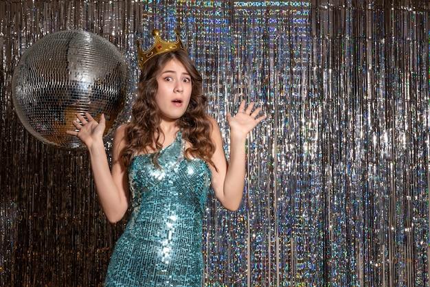 Młoda nerwowa emocjonalna piękna pani ubrana w niebiesko-zieloną błyszczącą sukienkę z cekinami z koroną na imprezie