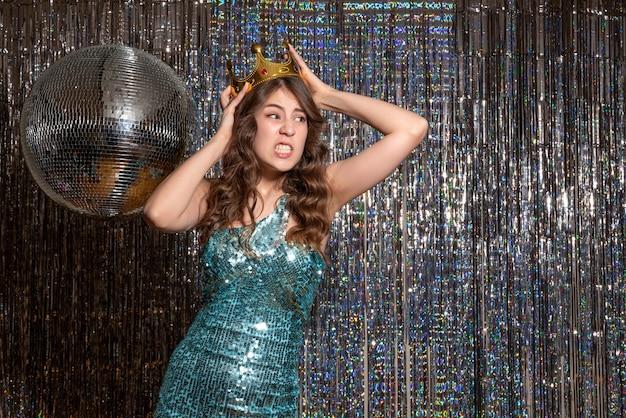 Młoda nerwowa niezadowolona piękna pani ubrana w niebiesko-zieloną błyszczącą sukienkę z cekinami z koroną na przyjęciu