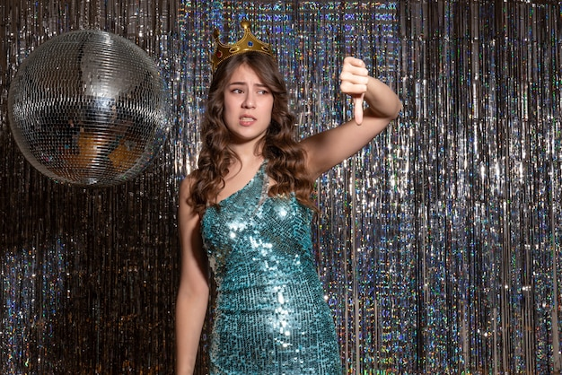 Młoda nerwowa piękna pani ubrana w niebiesko-zieloną błyszczącą sukienkę z cekinami z koroną skierowaną w dół na imprezie