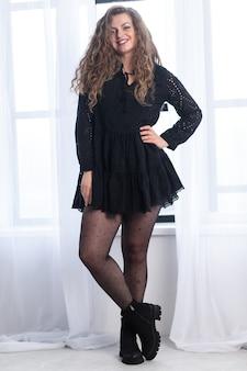 Młoda nie szczupła dziewczyna w czarnej sukience. gruba młoda kobieta. białe tło. moda pulchna kobieta