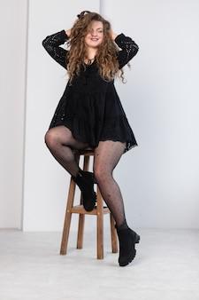 Młoda nie szczupła dziewczyna w czarnej sukience.