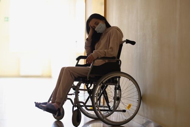 Młoda niepełnosprawna kobieta w ochronnej masce medycznej siedzi na wózku inwalidzkim w szpitalnym korytarzu