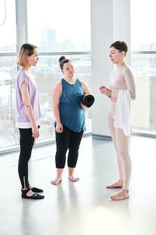 Młoda niepełnosprawna kobieta z czarną zwiniętą matą i jej przyjaciółka konsultująca się z instruktorem fitness po treningu na siłowni