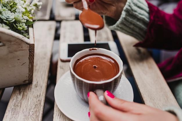 Młoda nierozpoznawalna kaukaska kobieta cieszy się gorącą czekoladą na tarasie z przyjaciółmi