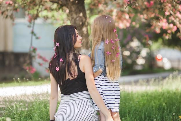 Młoda nierozpoznawalna kobieta z córeczką stojącą w parku z kwiatami we włosach. matka i mała dziewczynka na zewnątrz. szczęśliwa rodzina.